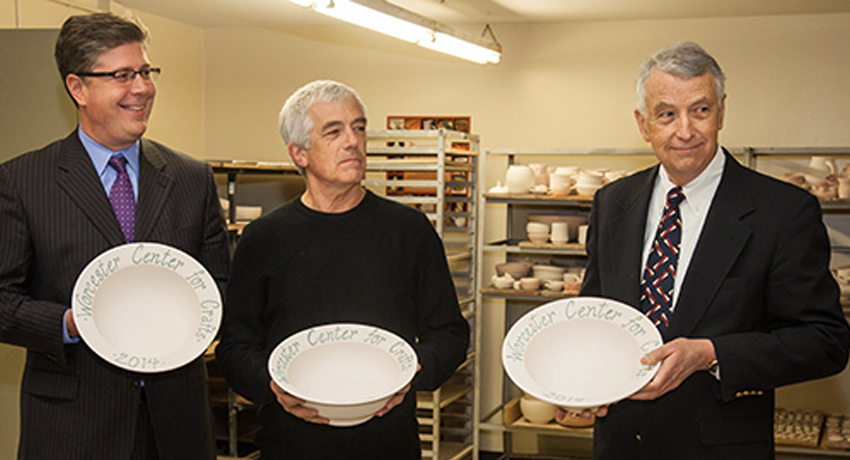 A photo of Worcester State University President Barry Maloney, Fletcher Foundation trustee Allen Fletcher and Stoddard Charitable Trust Chairman Warner Fletcher hold special bowls made in the newly renovated ceramics studio at Worcester Center for Crafts.