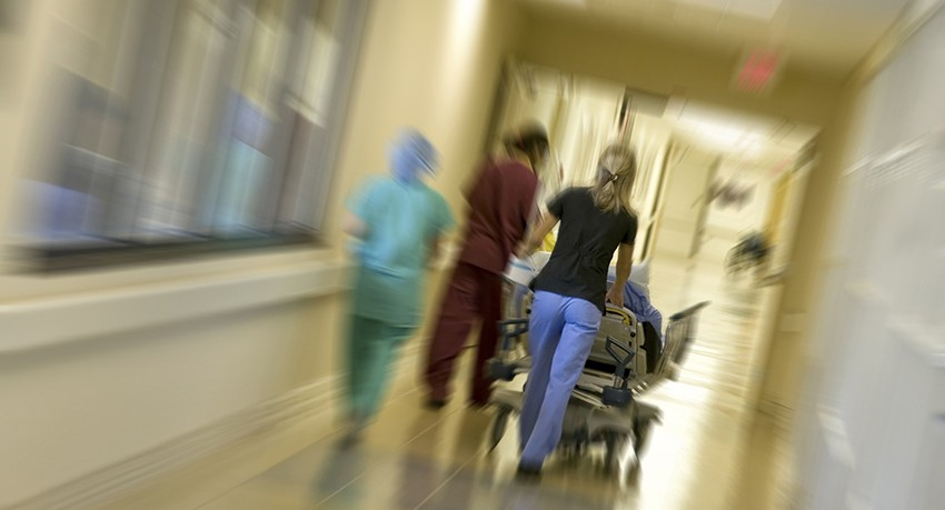 Nurses rushing through hall with patient