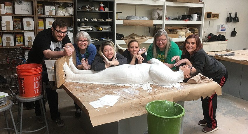 Worcester State University students in the CitySpeak Sculpture class. The plaster over the student lying on the table forms the cast.
