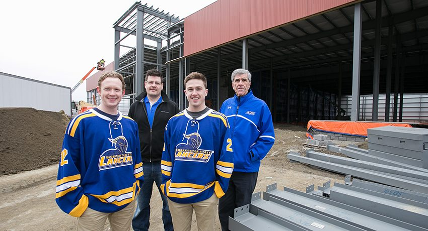 A few members of the Worcester State University men's hockey team and coaches in front of new ice rink