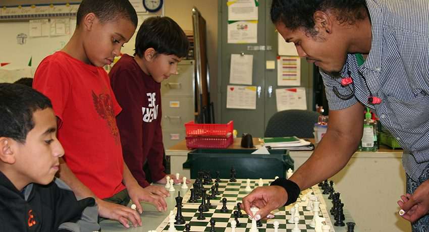 Worcester State senior Diallo Frys plays chess with City View students.