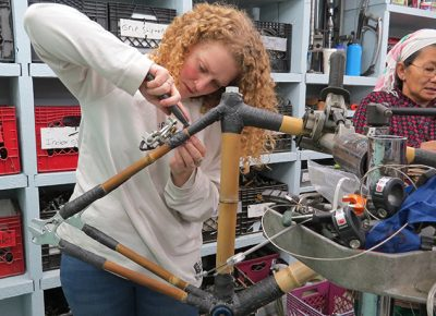 A participant in the Worcester bamboo bike workshop works on a bike.