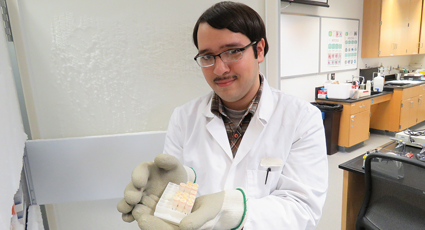 Worcester State biotech major Will Rodriguez holds Antarctica soil samples.