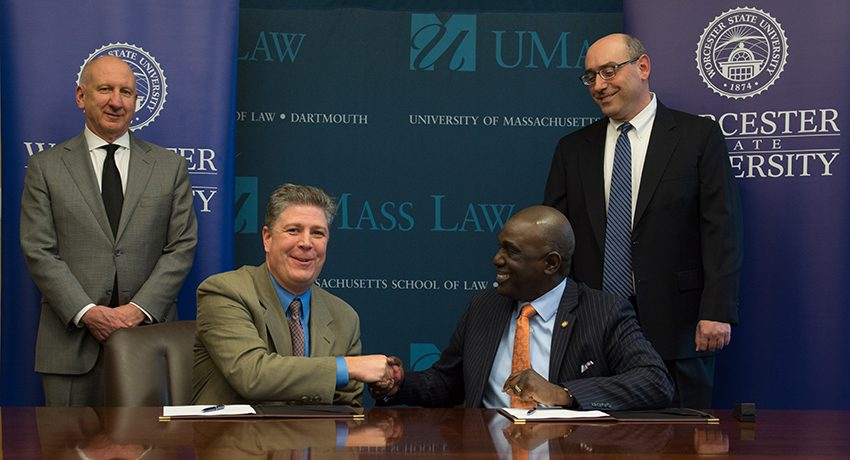 Worcester State President Barry Maloney shakes hands with UMass Dartmouth Chancellor Robert Johnson.