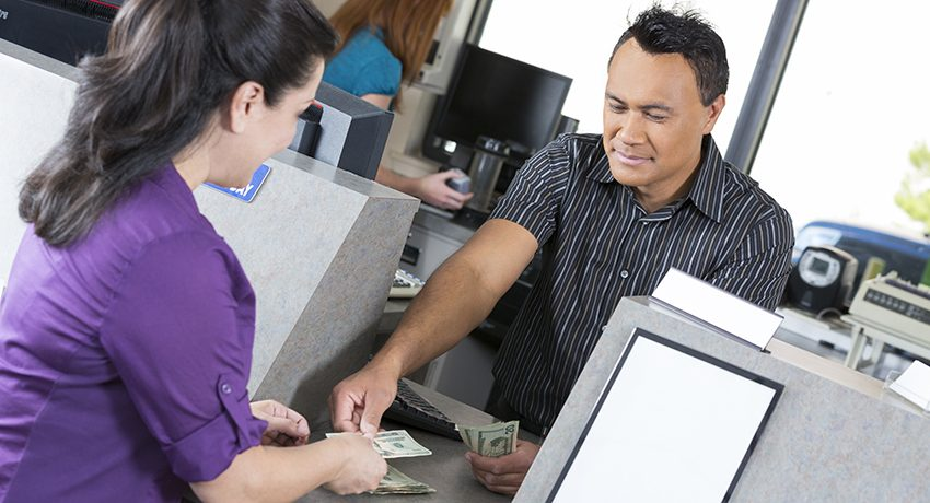 A man gets money from a bank teller.