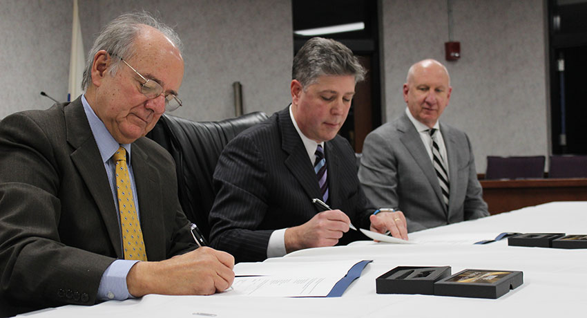 (from left) WNEU President Anthony S. Caprio, President Maloney and Russ Pottle at the agreement signing in Springfield at the Blake Law Center at WNEU Dec. 14.