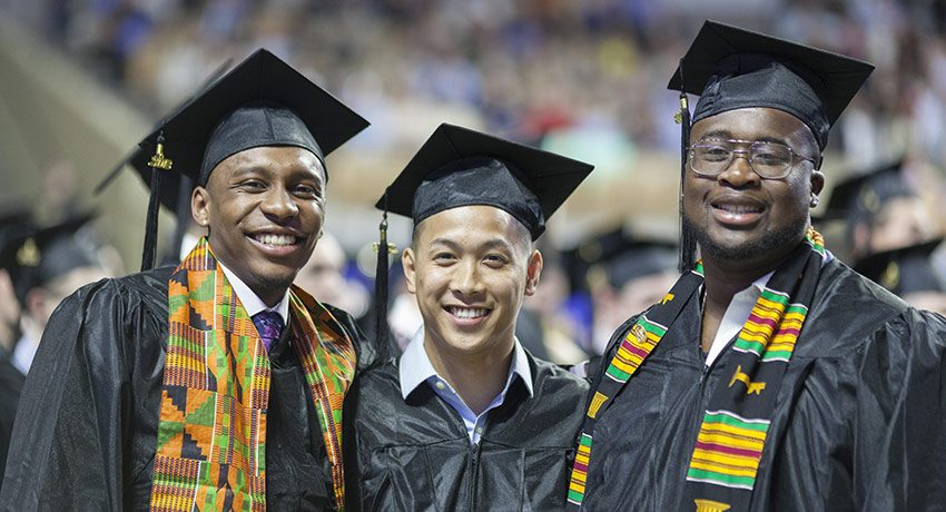 Three students pose at undergraduate commencement.