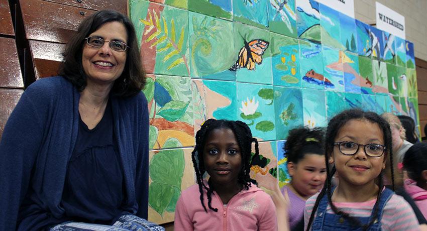 Pamela Hollander sit with May Street Elementary School students.
