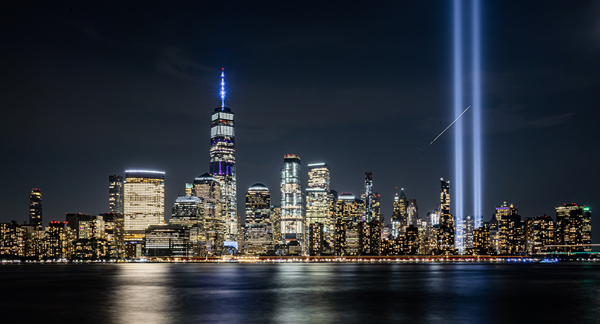 New York City skyline at night, with buildings lit up and the lights from the 9/11 Memorial going up into the sky