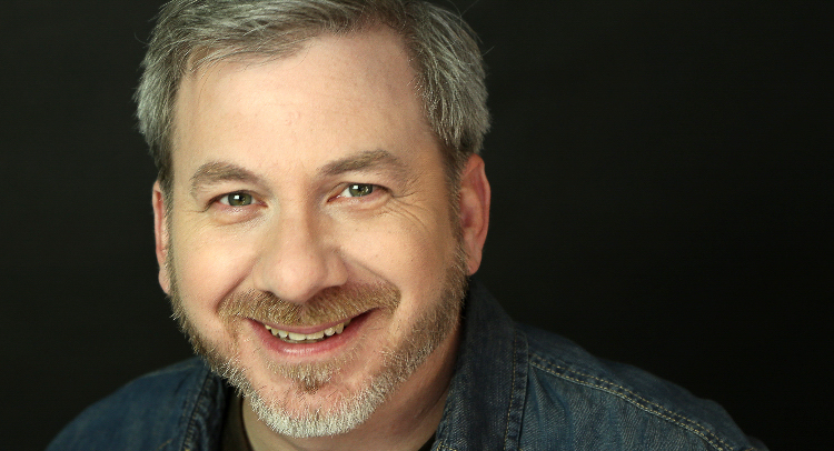 A close shot of Steve Gagliastro smiling into the camera in front of a black background. He has short hair and a beard and mustache and is wearing a dark denim shirt.