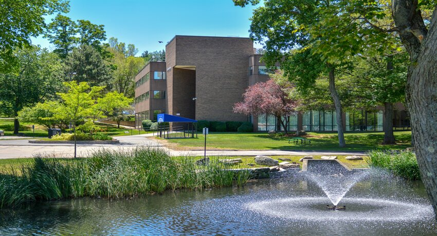 In the foreground, a fountain and pond, surrounded by green trees and grass. A brick building is in the background.