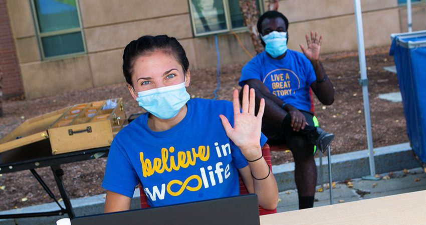 Two students wearing masks and blue t-shirts wave to the camera.