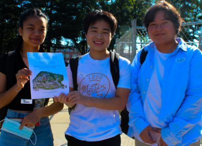 Three students stand outside on a sunny day, smiling at the camera and holding a sheet of paper with the WSU campus map and the words,