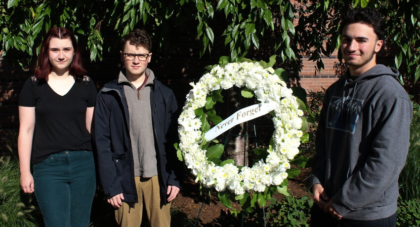 Renee Mercier '22, Preston Carr '22, and Daniel Bourget '25 stand next to a memorial wreath of white flowers with a ribbon that says,