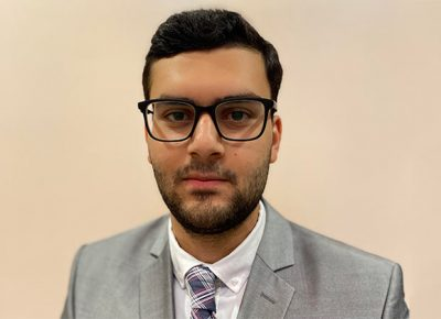 Zakery Dabbagh, wearing glasses and grey suit, looks into camera.